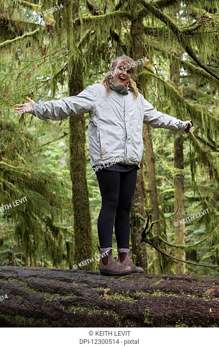 A young woman stands on a log in a forest with arms outstretched; Tofino, British Columbia, Canada