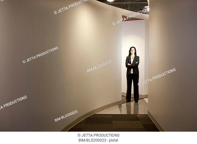 Mixed race businesswoman standing in office hallway