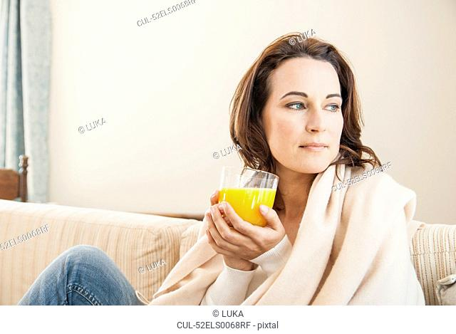 Woman having cup of juice on sofa