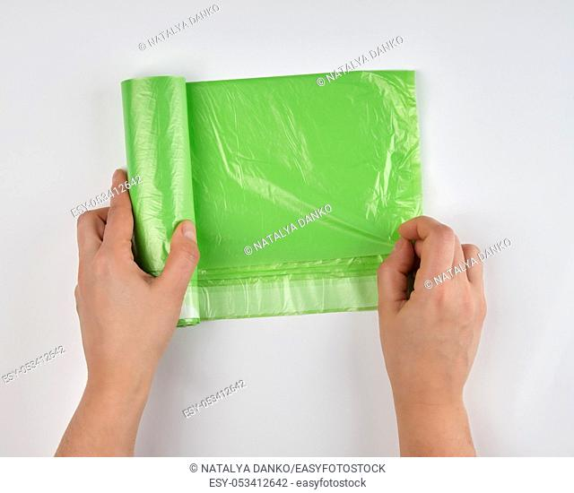 female hands unwinding a roll with polyethylene green bags for garbage on a white background, top view