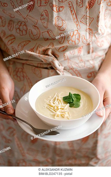 Woman holding bowl of cheese soup