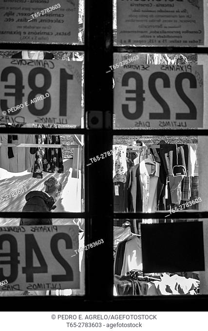 Street stalls and clothing prices in Euros, seen through a window, for the market in Melide in La Coruna