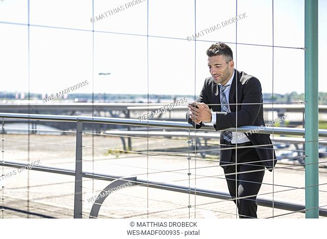 Businessman with cell phone at the airport