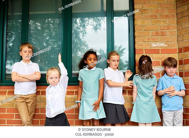 Schoolgirls and boys standing outside primary school building