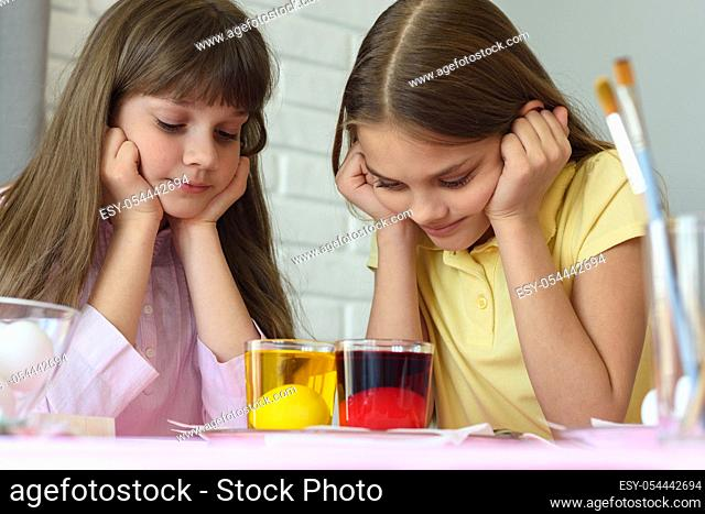 Children look in glasses with liquid dye while egg staining