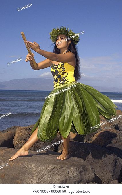 Hula dancer with haku lei in traditional outfit on rocky coast holding kala'au (sticks), ocean background