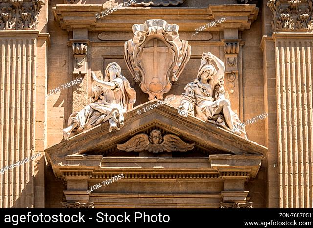 In the picture a marble statue of the Middle Ages showing two women, in the historic center of Florence