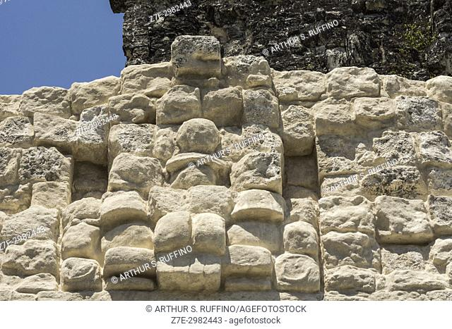 Detail of carved masks (faces) above the summit shrine of Temple II, Temple of the Masks, Tikal, Guatemala, Central America