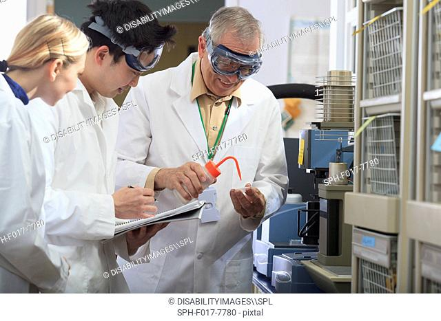 Professor working with engineering students adding ethanol to sample tray in a laboratory
