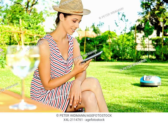 young beautiful woman in garden, mowing robot (model-released)