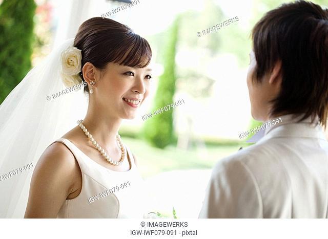 newlywed couple holding bouquet, smiling