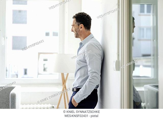 Smiling businessman in office leaning against wall at the window