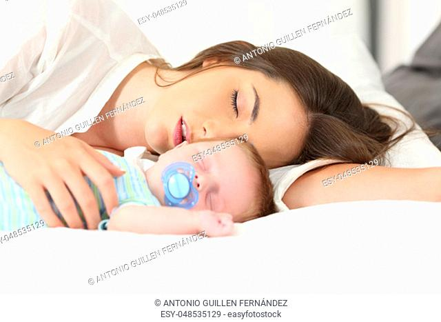 Tired mother sleeping with her baby on a bed at home