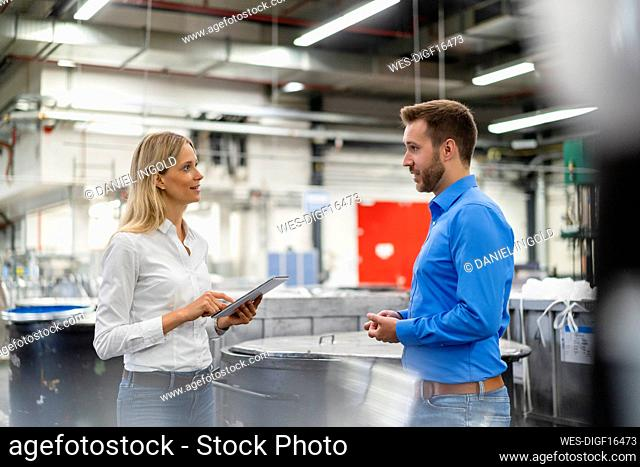 Young businesswoman holding digital tablet while discussing with colleague in factory