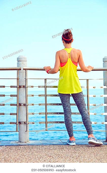 Look Good, Feel great! Seen from behind young woman in fitness outfit standing at the embankment