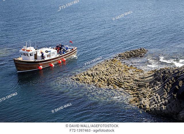 Staffa tour boat and polygonal basalt, Am Buachaille rocks, Staffa, Scotland, United Kingdom