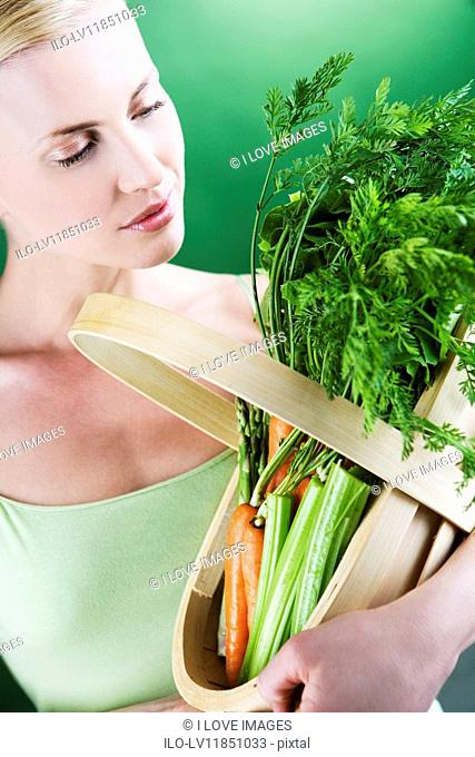 A young woman looking at a basket full of vegetables