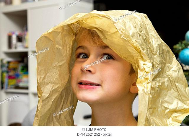 Portrait of a young boy with a piece of wrapping paper on his head making a silly face; Langley, British Columbia, Canada