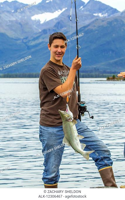 A young man hoists a Silver salmon on the shore while fishing in Port Valdez, Southcentral Alaska