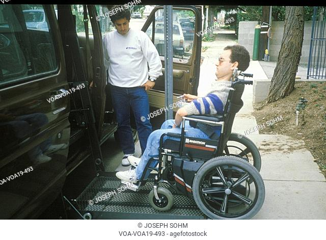 Wheelchair bound young man getting into specially equipped van