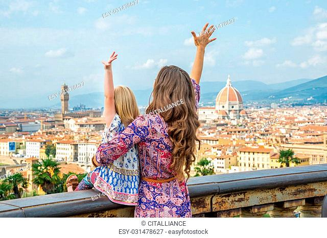 Mother and baby girl looking on panoramic view of florence, italy and rejoicing
