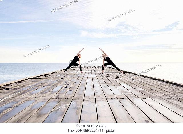 Women exercising yoga on pier