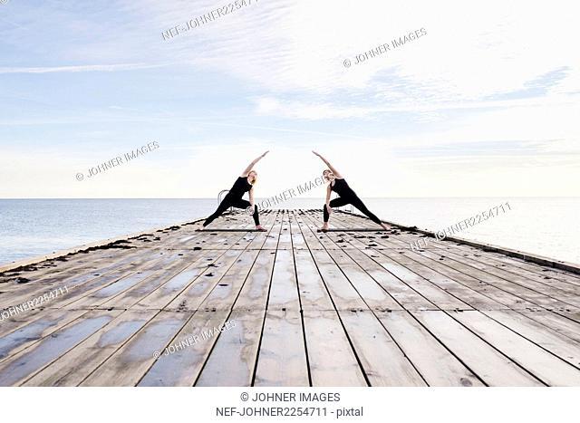 Women exercising yoga on pier