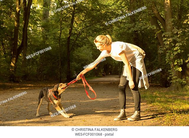 Young woman playing with her dog on a forest track