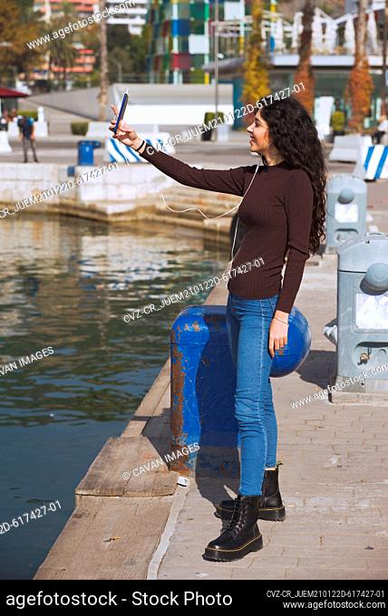 Young woman drives the mobile on the port dike next to the water
