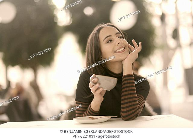 portrait of woman holding coffee cup while enjoying break at table in café, in Munich, Germany