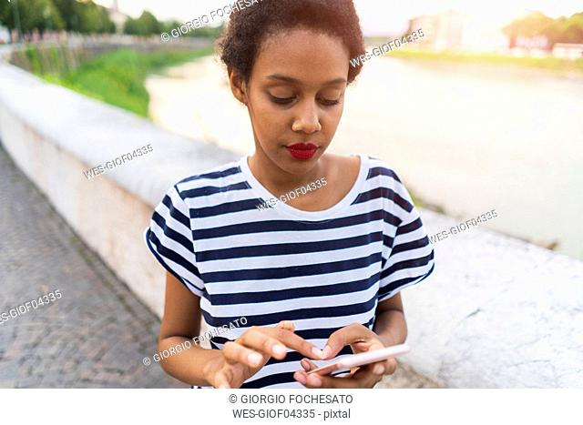Young woman at the riverside using cell phone