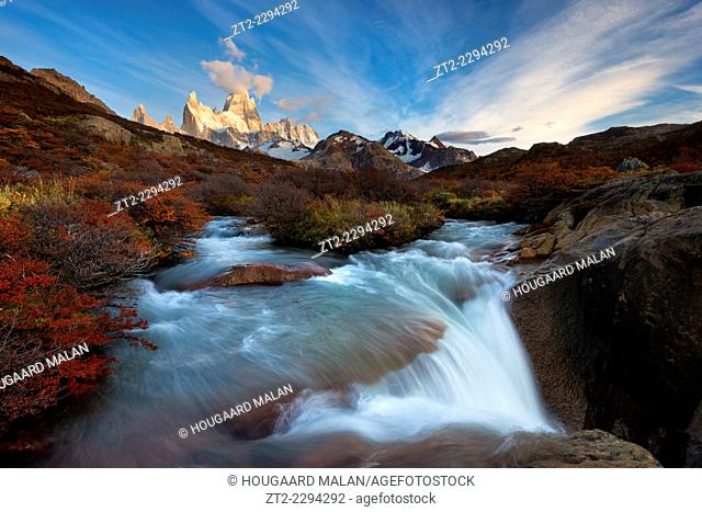Landscape image of a waterfall below mount Fitz Roy in warm morning light. El Chalten, Patagonia, Argentina
