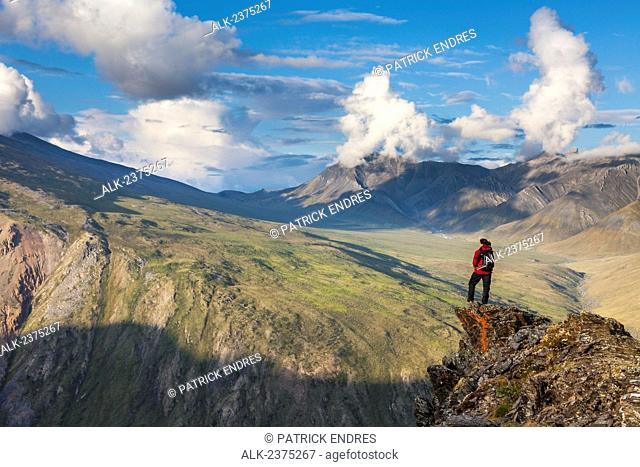 Hiker in the Brooks range mountains bordering the west side of the Marsh Fork of the Canning river in the Arctic National Wildlife Refuge in the Brooks range...