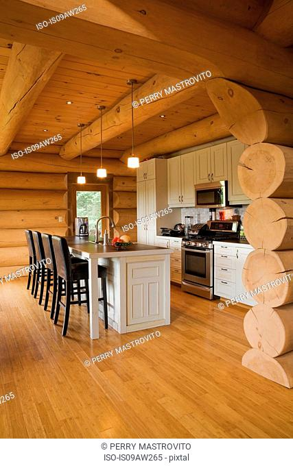 White kitchen cabinets and island and barstools in kitchen of a Scandinavian cottage style log home