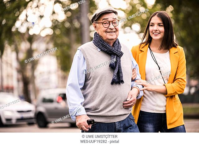 Portrait of senior man strolling together with his adult granddaughter