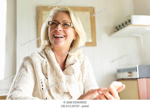 Smiling senior woman in sweater texting with cell phone in kitchen