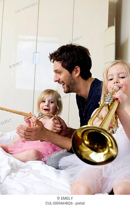 Father and two young daughters playing music