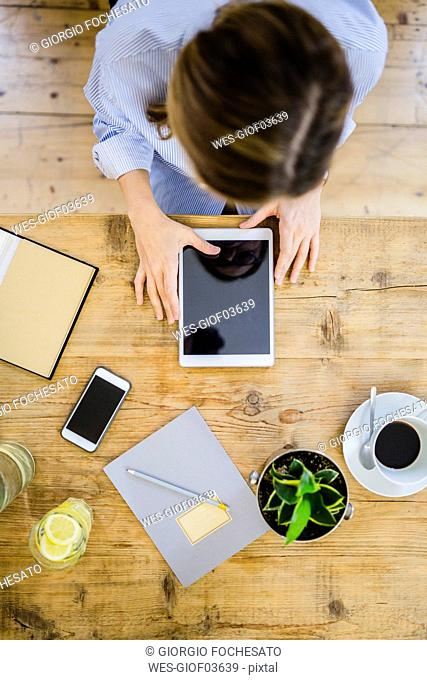 Top view of woman at wooden desk with notebook, cell phone and tablet