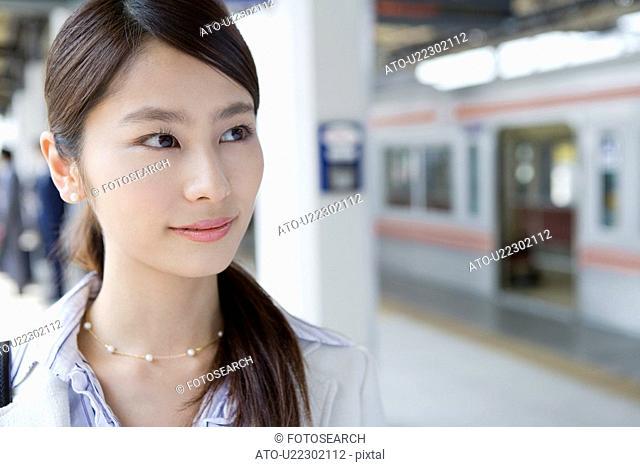 Young woman at platform, smiling, close up