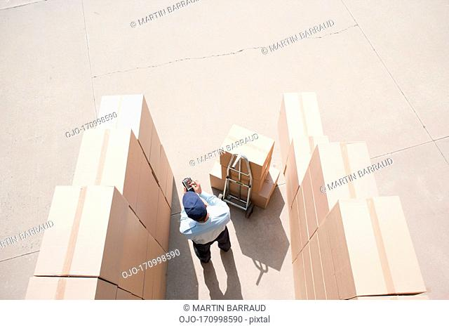 Worker standing with boxes and hand truck