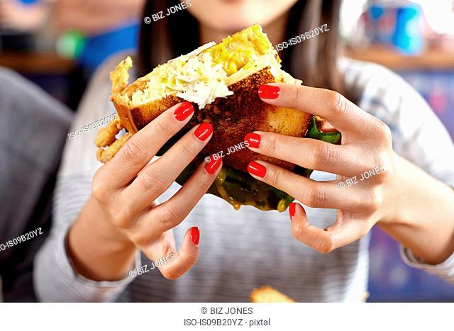 Young woman eating fast food, mid section, close-up