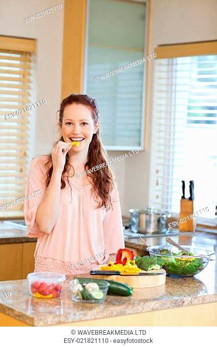 Woman nibbling bell pepper while preparing healthy salad