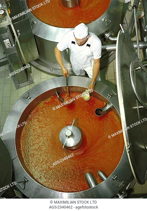 Agriculture - Food production industry; a food technician takes a sample from a boiling vessel used in the production of soups and sauces / Europe
