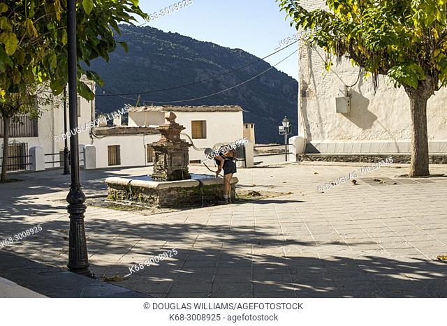A woman at a fountain in a plaza next to the church in the village of Bubion, Alpujarras, Spain
