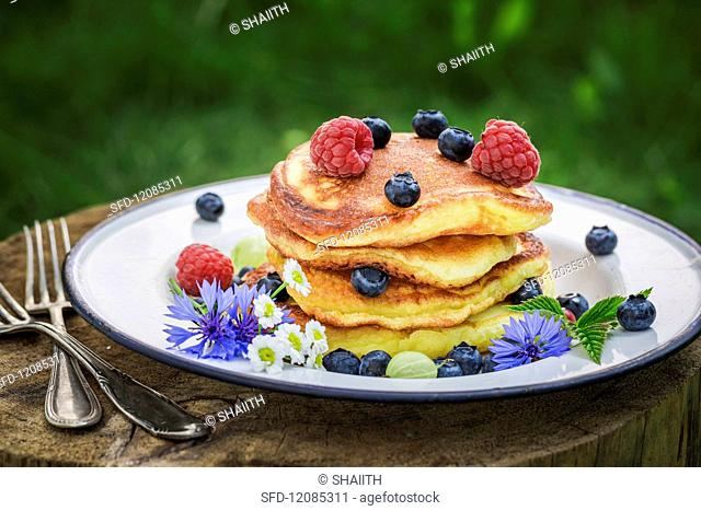 A stack of pancakes with fresh berries and maple syrup