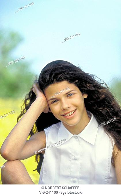 portrait, smiling girl with long brown hair, 13 years, wearing white sleeveless blouse and shorts, sits on a meadow sprinkeled with yellow flowers  - GERMANY