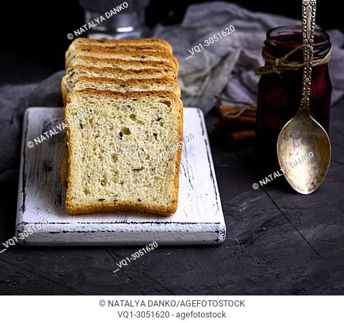 Square pieces of bread from white wheat flour with flax seeds on a wooden board next to a jar and an iron spoon