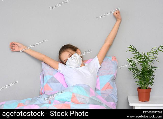 A recovering girl in a medical mask woke up in the morning and stretches herself in bed