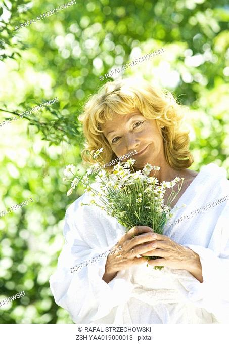 Senior woman wearing bathrobe, holding flowers, outdoors