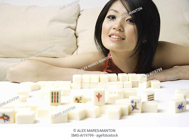 Young woman smiling at camera, mahjong tiles on table in front of her